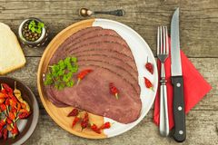Cold roast beef on a wooden table. Delicacy of beef. Preparing cold refreshments. Traditional meal. Royalty Free Stock Photo