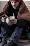 Cold and sad homeless man is eating a bread Royalty Free Stock Photography