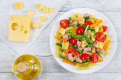 Cold salad of italian pasta fusilli. Delicious salad of italian pasta fusilli with carrot and zucchini sticks, ham, cheese chunks, green peas, cherry tomatoes on Royalty Free Stock Photos