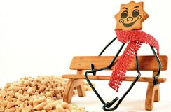 Cold season. Closeup of a sunny wooden figure with a red scarf and pellets in front Royalty Free Stock Photo