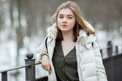 Cold season young beautiful woman in white coat with disheveled hair posing on park bridge lifestyle concept portrait Stock Photos