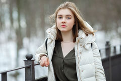 Cold season young beautiful woman in white coat with disheveled hair posing on park bridge lifestyle concept portrait Royalty Free Stock Image