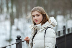 Cold season young beautiful woman in white coat posing on park bridge lifestyle concept portrait Stock Photos