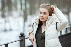 Cold season young beautiful woman in white coat touching hair posing on park bridge lifestyle concept portrait Royalty Free Stock Images