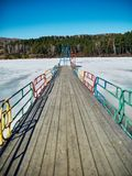 Cold Siberian landscape of a lake strained in the ice. Frozen lake and the path to the diving tower royalty free stock photos