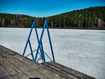Cold Siberian landscape of a lake strained in the ice. Frozen lake and ladder for diving into the water royalty free stock photography