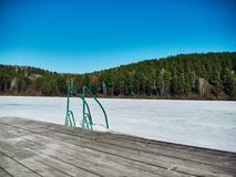 Cold Siberian landscape of a lake strained in the ice. Frozen lake and ladder for diving into the water stock image