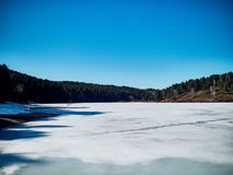 Cold Siberian landscape of a lake strained in the ice. Frozen lake and the path to the diving tower stock photo