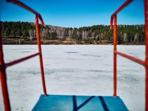 Cold Siberian landscape of a lake strained in the ice. View of the road on the back side of the frozen lake through the handrails of the tower for diving stock images