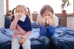 Ill little girls blowing their noses. Cold. Sick little fair-haired sisters sitting on the bed and blowing their noses and sneezing and wearing scarfs Stock Photos