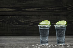 Cold silver tequila with white crystals of salt on a black woode Stock Image