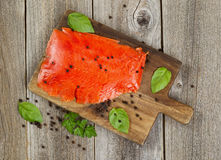 Cold smoke red salmon being prepared on wooden server board Stock Image