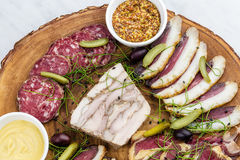 Cold smoked meat plate with, proscius on white wooden desk. Royalty Free Stock Images