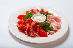 Cold smoked meat plate with prosciutto, salami, bacon, ham and sauce on a white plate. Stock Image