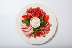 Cold smoked meat plate with prosciutto, salami, bacon, ham and sauce on a white plate. Royalty Free Stock Photography