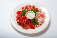 Cold smoked meat plate with prosciutto, salami, bacon, ham and sauce on a white plate. Stock Photography