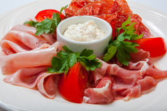 Cold smoked meat plate with prosciutto, salami, bacon, ham and sauce on a white plate. Royalty Free Stock Image