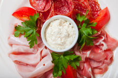 Cold smoked meat plate with prosciutto, salami, bacon, ham and sauce on a white plate. Stock Images