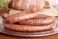 Cold smoked sausage. Natural prepared slow food smoked ring-shaped sausage, cured pork shoulder which looks similar to ham in the background Stock Photography