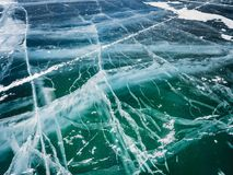 Network of cracks in thick solid layer of ice of a frozen Baikal lake in Siberia. Cold and smooth transparent ice surface looks like abstract texture stock photography
