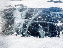 Network of cracks in thick solid layer of ice partially covered by snow of a frozen surface Baikal lake in Siberia. Cold and smooth transparent ice surface looks royalty free stock photo