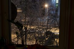 Cold and snowy night in Vilnius. Lithuania. View through the window stock images