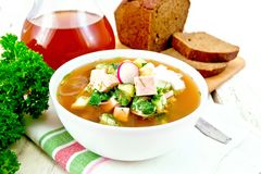 Okroshka in white bowl on towel. Cold soup okroshka from sausage, potato, egg, radish, cucumber, greens and kvass in a white bowl on napkin, bread and jug with Royalty Free Stock Photography