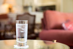 Cold sparkling glass of water detail. Cold sparkling glass of water with ice cubes in a cosy bar Royalty Free Stock Images