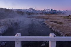 Cold steam rising from a creek seen from a white picket bridge stock photos