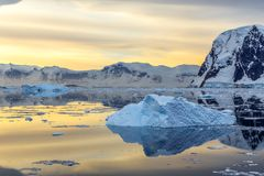 Cold still water of antarctic lagoon with drifting blue icebergs. And mountains in the background, Antarctica Stock Image