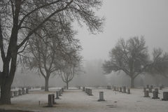 Cold Stones. Rows of granite markers in a cold foggy cemetary stock image