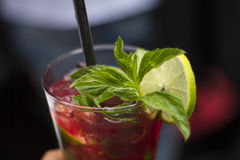 Cold strawberry cocktail - Stock Image. Cold strawberry cocktail with mint leaves, ice and lime Royalty Free Stock Photography