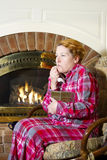 Cold Sufferer. Mature woman dressed in flannel pajamas sitting in a chair in front of a fireplace in the home taking her temperature with an oral thermometer Stock Image