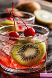 Cold summer cocktail drink with cherry and kiwi Stock Photos