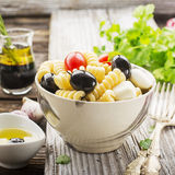 Cold summer pasta salad, black olives, mozzarella, juicy tomatoes and mint leaves in a ceramic marble bowl on a simple. Wooden background with herbs and olive Royalty Free Stock Photo