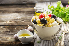 Cold summer pasta salad, black olives, mozzarella, juicy tomatoes and mint leaves in a ceramic marble bowl on a simple. Wooden background with herbs and olive Royalty Free Stock Image