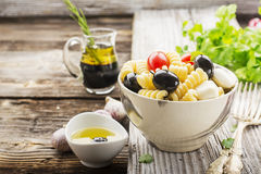 Cold summer pasta salad, black olives, mozzarella, juicy tomatoes and mint leaves in a ceramic marble bowl on a simple. Wooden background with herbs and olive Royalty Free Stock Photography
