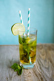 Cold  tea cocktail with ice and straw on board Royalty Free Stock Photo