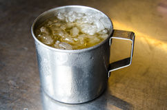 Cold tea with ice in glass. On stainless table Stock Photo