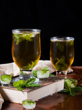 Cold tea with ice and mint leaves on dark background Stock Photography