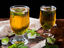 Cold tea with ice and mint leaves on dark background Royalty Free Stock Photography