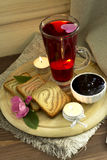Cold tea with toasts and jam. Flower tea with toasts, jam and candles on a wooden support Royalty Free Stock Photography