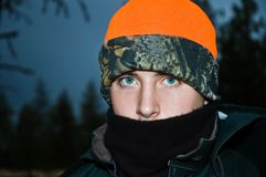 Cold teenage male portrait. A teenage boy on his first early morning deer hunt, dressed for the cold weather royalty free stock photo