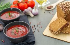 Cold tomato gazpacho soup in a deep plate on a stone background. stock image