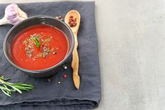 Cold tomato gazpacho soup in a deep plate on a stone background. royalty free stock photography