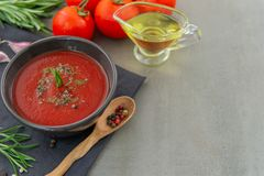 Cold tomato gazpacho soup in a deep plate on a stone background royalty free stock photo