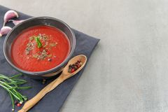 Cold tomato gazpacho soup in a deep plate on a stone background. T stock photo