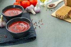 Cold tomato gazpacho soup in a deep plate on a stone background. stock photography
