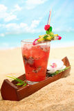 Cold tropical fruit cocktail on a beach Royalty Free Stock Image