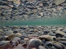Cold underwater river bed with perfect reflection on surface. Tension Royalty Free Stock Photos